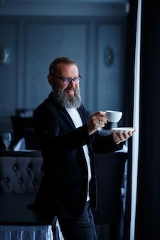 Dorosły mężczyzna mentor, reżyser, biznesmen w okularach i garniturze pije kawę i odpoczywa. koncepcja dnia roboczego