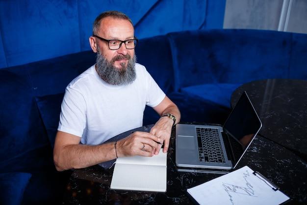Dorosły mężczyzna mentor, reżyser, biznesmen w okularach i garniturze studiujący dokumenty siedząc przy stole. koncepcja dnia roboczego