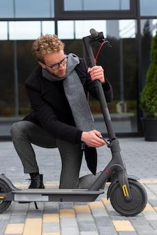 Dorosły mężczyzna naprawiający jego skuter elektryczny