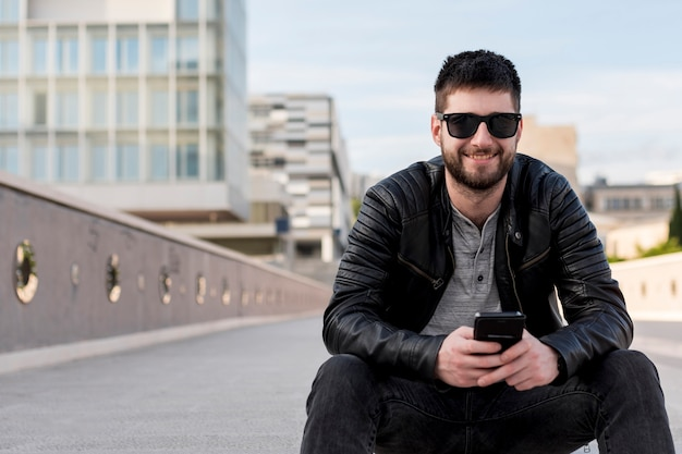 Dorosły mężczyzna obsiadanie na zmielonym mienia smartphone