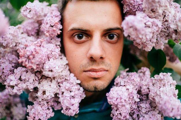 Dorosły mężczyzna otoczony kwitnącymi kwiatami