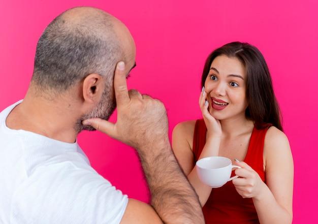 Dorosły mężczyzna para dotykając głowy rozmawia z kobietą i pod wrażeniem kobiety trzymającej kubek dotykając twarzy, patrząc na siebie