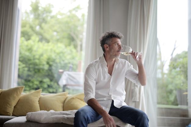 Dorosły mężczyzna pijący kieliszek białego wina w świetle słonecznym przez okna