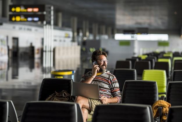 Dorosły mężczyzna podróżujący na lotnisku siada przy bramce, czekając na lot samolotem