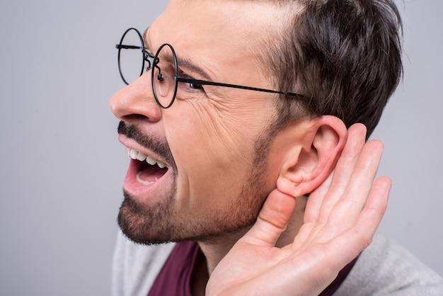 Dorosły mężczyzna potajemnie słucha prywatnej rozmowy.