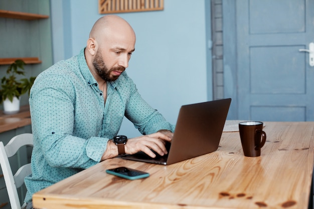 Dorosły mężczyzna pracuje przy komputerze podczas porannej kawy, pracuje w domu
