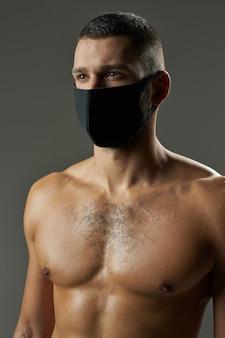 Dorosły mężczyzna rasy kaukaskiej o potężnym ciele pozuje do kamery w studio