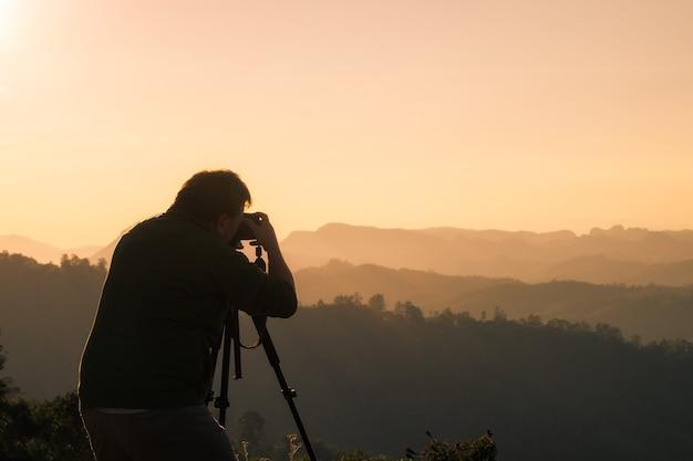 Dorosły mężczyzna robi zdjęcie aparatem dslr na szczycie góry o wschodzie słońca rano