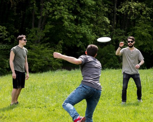 Dorosły mężczyzna rzuca frisbee dla przyjaciela w parku