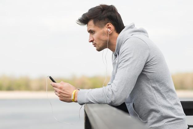 Dorosły mężczyzna sprawdza jego telefon komórkowego