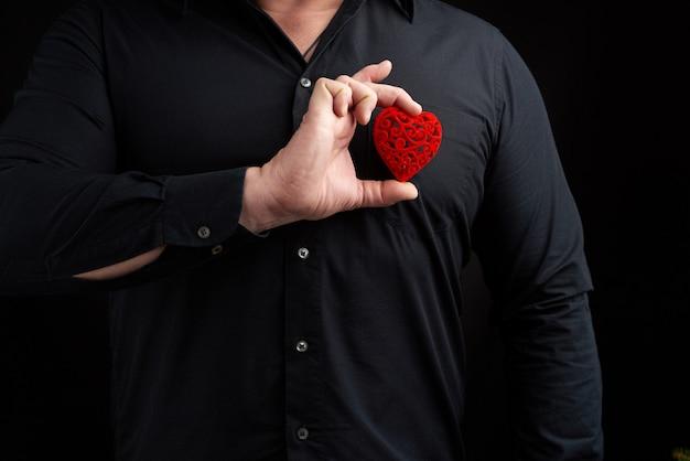 Dorosły mężczyzna stoi na ciemności w czarnej koszuli i trzyma czerwone rzeźbione serce przy piersi