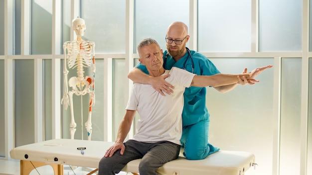 Dorosły mężczyzna trenuje siłę mięśni pod okiem profesjonalnego lekarza w nowoczesnej klinice rehabilitacji fi...