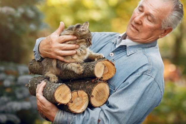Dorosły mężczyzna trzyma drewno opałowe i kota