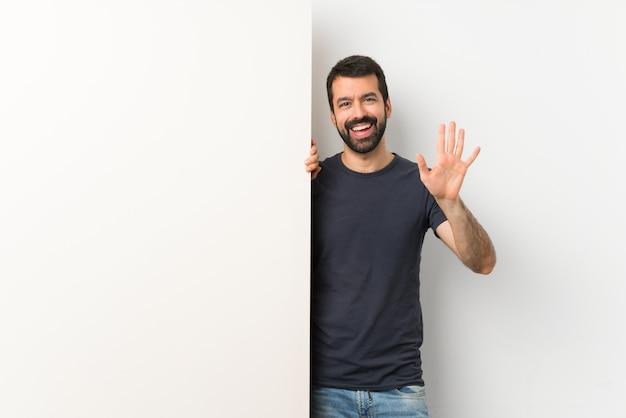 Dorosły mężczyzna trzyma duży pusty plakat i salutuje