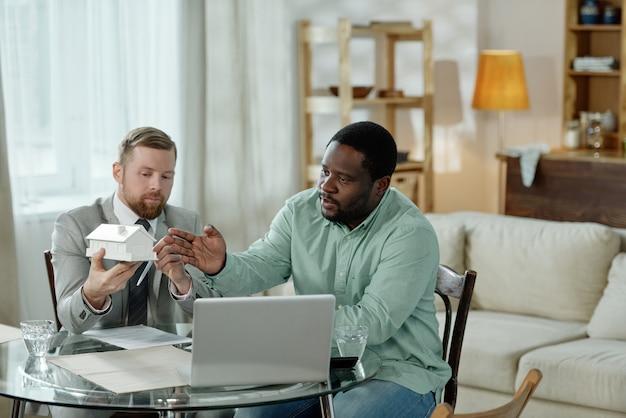 Dorosły mężczyzna trzyma makieta domu i doradza murzyn w sprawie kredytu mieszkaniowego siedzi przy stole