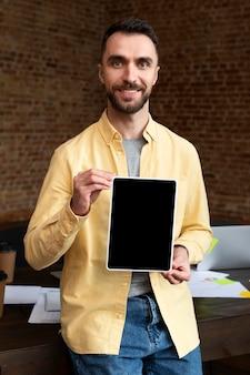 Dorosły mężczyzna trzyma tablet w biurze
