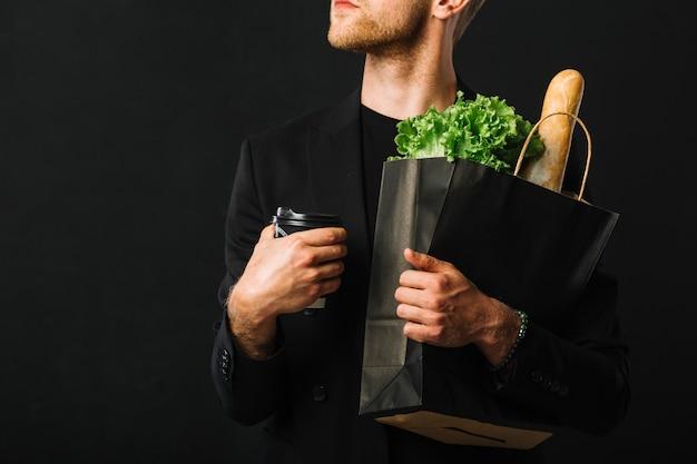 Dorosły mężczyzna trzyma torbę na artykuły spożywcze