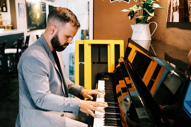 Dorosły mężczyzna ubrany w szary garnitur gra na pianinie w barze