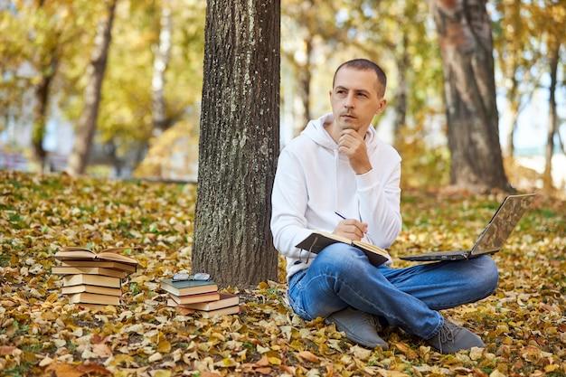 Dorosły mężczyzna w białej bluzie z kapturem uczy się w parku na laptopie pisze w zeszycie czyta książki i podręczniki nauka dystansu społecznego na świeżym powietrzu
