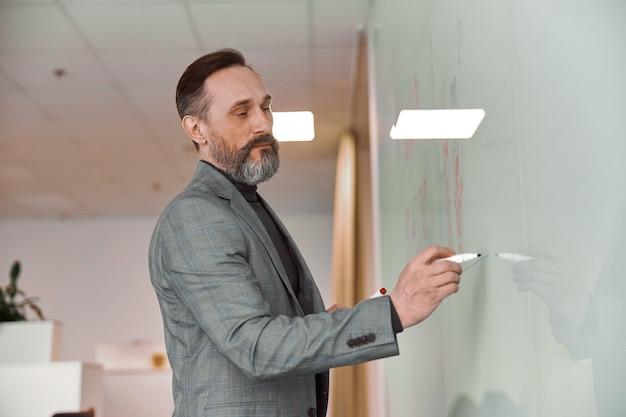Dorosły mężczyzna w biurze pisze na szklanym biurku
