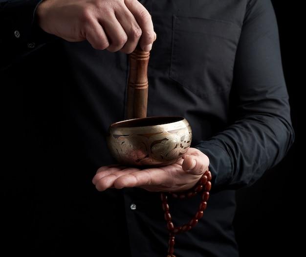 Dorosły mężczyzna w czarnej koszuli obraca drewniany patyk wokół miedzianej misy tybetańskiej