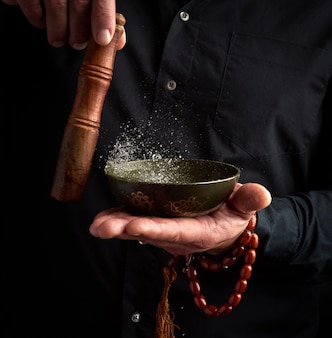 Dorosły mężczyzna w czarnej koszuli obraca drewniany patyk wokół miedzianej tybetańskiej miski z wodą