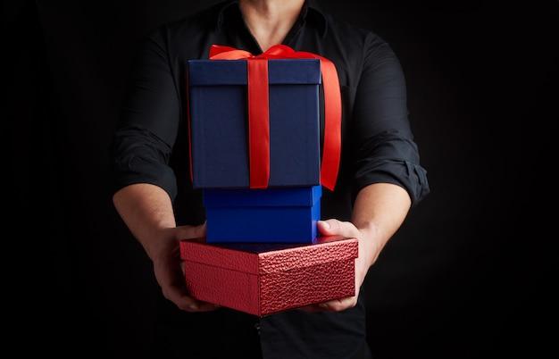 Dorosły mężczyzna w czarnej koszuli trzyma w rękach stos prezentów zawiniętych w papier