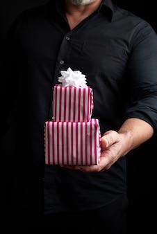 Dorosły mężczyzna w czarnej koszuli trzyma w ręku stos prezentów zawiniętych w papier