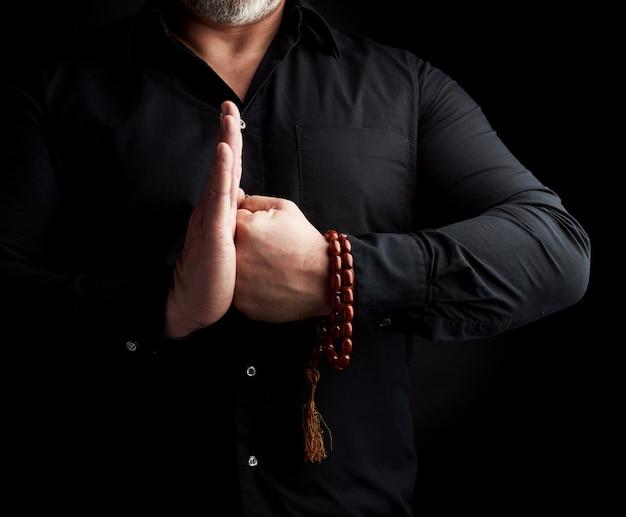Dorosły mężczyzna w czarnych ubraniach połączył ręce przed klatką piersiową