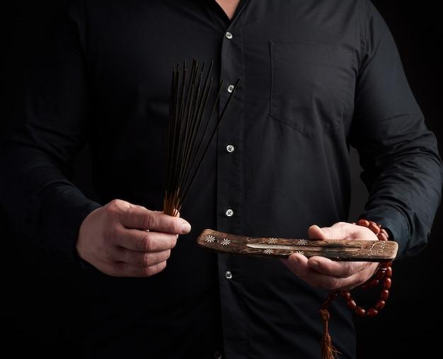 Dorosły mężczyzna w czarnych ubraniach trzyma stos kadzidełek