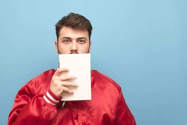 Dorosły mężczyzna w czerwonej kurtce stoi na niebiesko z białą książką w ręku