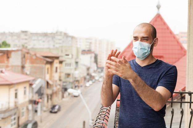 Dorosły mężczyzna w masce ochronnej klaszcze na balkonie, pokazując wsparcie dla personelu medycznego w walce z koronawirusem.