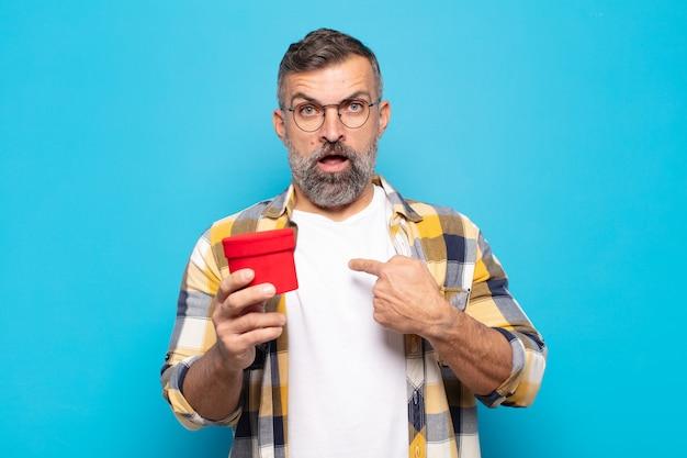 Dorosły mężczyzna wyglądający na zszokowanego i zaskoczonego z szeroko otwartymi ustami, wskazujący na siebie