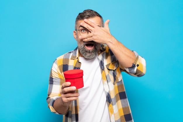 Dorosły mężczyzna wyglądający na zszokowanego, przestraszonego lub przerażonego, zakrywający twarz dłonią i zaglądający między palce