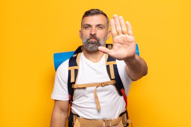 Dorosły mężczyzna wyglądający poważnie, surowo, niezadowolony i zły pokazuje otwartą dłoń wykonującą gest stopu