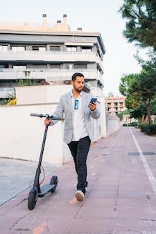 Dorosły mężczyzna z ameryki łacińskiej w okularach przeciwsłonecznych, dobrze ubrany i skuter elektryczny rozmawia przez telefon komórkowy na ulicy