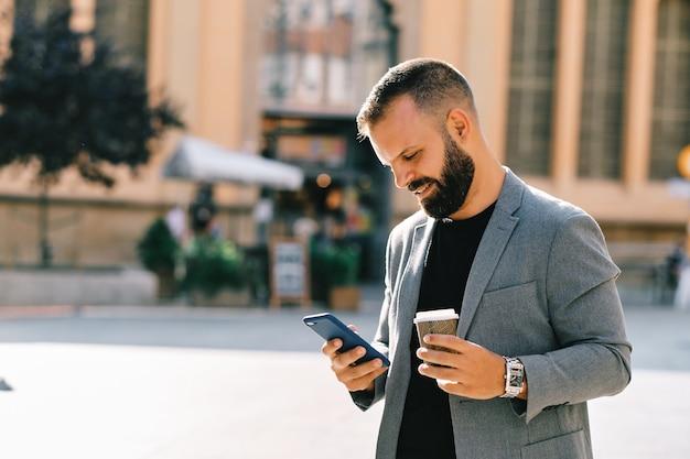 Dorosły mężczyzna z brodą i dorywczo szary garnitur przy użyciu telefonu komórkowego i picia kawy