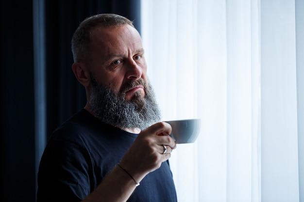 Dorosły mężczyzna z brodą pije kawę i wygląda przez okno. koncepcja rekreacji w terenie w dniu roboczym