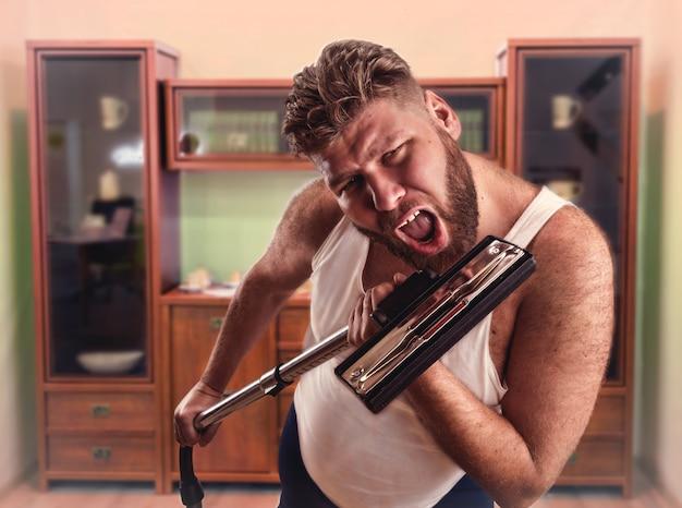 Dorosły mężczyzna z brodą śpiewa do odkurzacza
