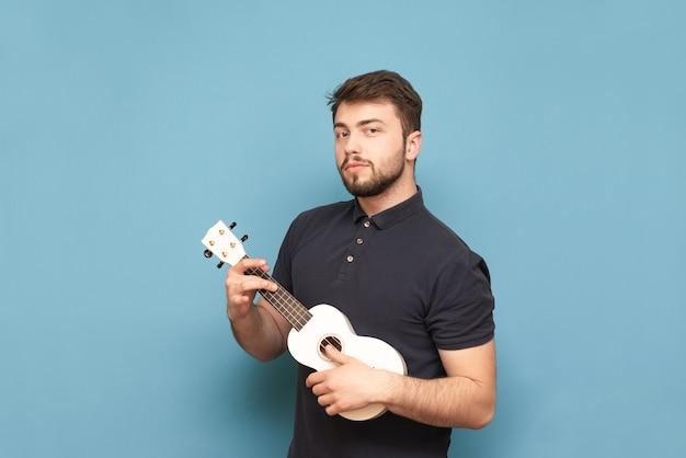 Dorosły mężczyzna z brodą w ciemnej koszulce gra na ukulele, odizolowane na niebiesko
