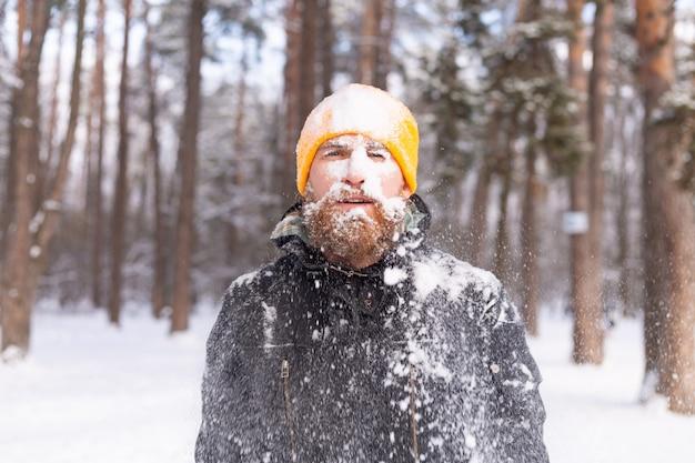 Dorosły mężczyzna z brodą w zimowym lesie twarzą w śniegu, zmarznięty, niezadowolony z zimna