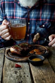 Dorosły mężczyzna z brodą zjada stek musztardowy i pije piwo