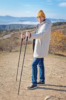 Dorosły mężczyzna z kijami do nordic walking stojący wysoko w górach na pełnej wysokości.