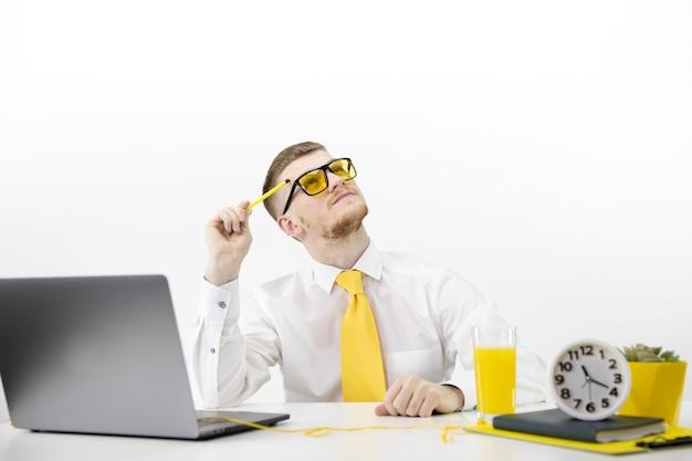 Dorosły mężczyzna z laptopem spogląda w zamyśleniu, akcentując żółty słoik z krawatem