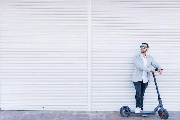 Dorosły mężczyzna z latynoskimi okularami przeciwsłonecznymi, dobrze ubrany i jeździ skuterem elektrycznym na ulicy