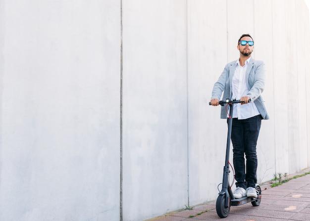 Dorosły mężczyzna z latynoskimi okularami przeciwsłonecznymi, dobrze ubrany i skuter elektryczny na ulicy na białym tle ślepy