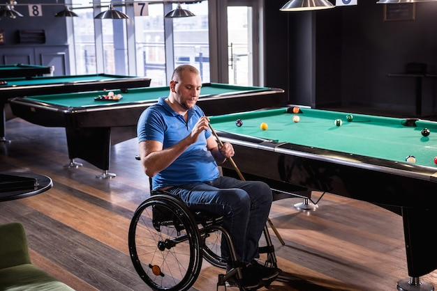 Dorosły mężczyzna z niepełnosprawnością na wózku inwalidzkim gra w bilard w klubie
