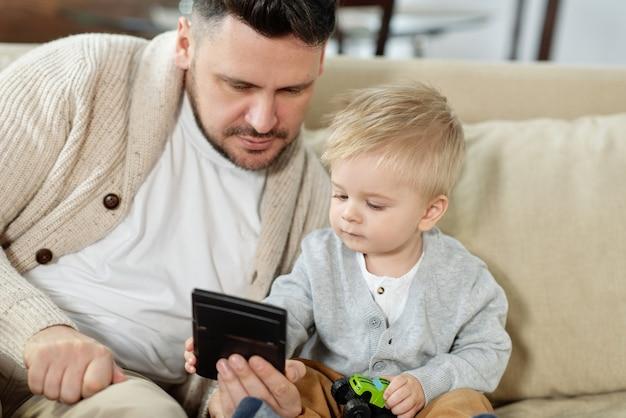 Dorosły mężczyzna z uroczym synkiem siedzi na kanapie oglądając razem gadżet