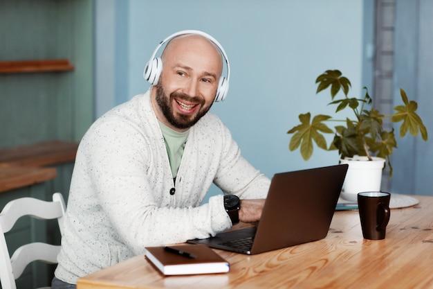 Dorosły mężczyzna ze słuchawkami pracuje przy komputerze w kuchni