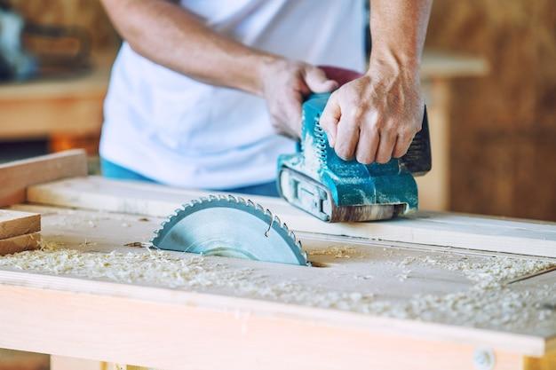 Dorosły młody człowiek pracujący w stolarni pracujący z narzędziami na produkcie